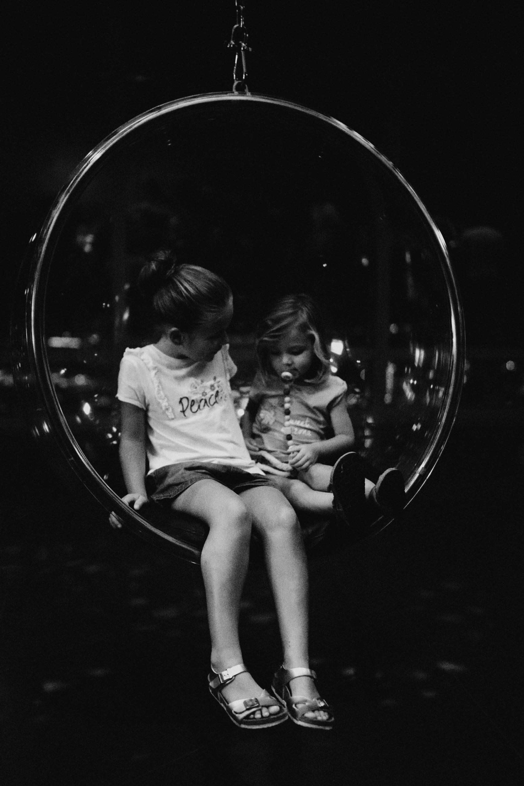 Deux petite fille dans un fauteuil rond suspendu
